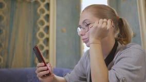 Giovane donna in vetri, sedentesi in un caffè asiatico, facendo uso di Internet in uno smartphone stock footage
