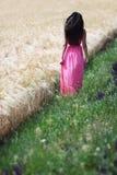 Giovane donna vicino ad un campo di frumento Immagine Stock