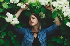 Giovane donna vicino al cespuglio dei fiori bianchi in un giardino immagine stock libera da diritti