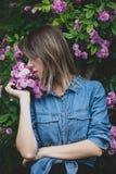 Giovane donna vicino al cespuglio dei fiori porpora in un giardino immagine stock libera da diritti