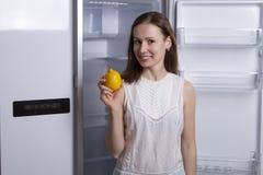 Giovane donna vicino al frigorifero vuoto con frutta Immagine Stock