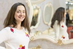 Giovane donna vicino al grande specchio immagini stock
