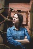 Giovane donna vicino alla ruota di vecchia mietitrebbiatrice di legno XIX del secolo immagini stock