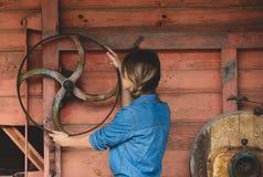 Giovane donna vicino alla ruota di vecchia mietitrebbiatrice di legno XIX del secolo fotografia stock libera da diritti