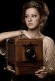 Giovane donna vicino alla vecchia macchina fotografica Immagini Stock