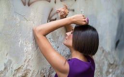Giovane donna vicino alla vecchia parete pfoto Fotografia Stock