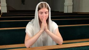 Giovane donna votata religiosa che prega nella chiesa battista Cattolico fedele alla cattedrale europea: dentro del luogo santo stock footage
