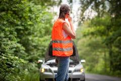 Giovane driver femminile che chiama il servizio del bordo della strada Fotografia Stock Libera da Diritti
