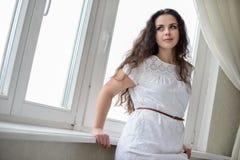 Giovane e bella donna castana che posa vicino alla finestra Fotografie Stock Libere da Diritti