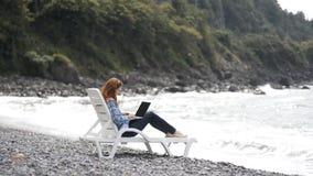 Giovane e bella donna che scrive sul computer portatile moderno vicino al mare archivi video