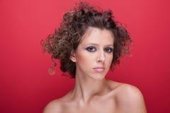 Giovane e bella donna, con capelli ricci, su colore rosso Immagine Stock