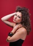 Giovane e bella donna, con capelli ricci, su colore rosso Immagini Stock Libere da Diritti