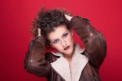 Giovane e bella donna, con capelli ricci, su colore rosso Fotografia Stock Libera da Diritti