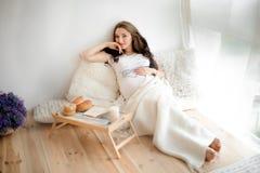 Giovane e bella donna incinta che si trova vicino alla finestra immagini stock libere da diritti