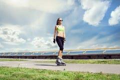 Giovane e donna adatta che rollerblading sui pattini fotografia stock libera da diritti
