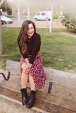 Giovane e donna allegra alla moda che si siede su un banco che ride timido fotografie stock libere da diritti