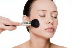 Giovane e donna attraente che applica blusher Immagine Stock