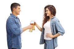 Giovane e donna che fanno acclamazioni con i vetri di birra immagini stock