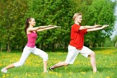 Giovane e donna che fanno allungando gli esercizi Immagini Stock