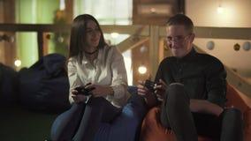 Giovane e donna che giocano video gioco che si siede nelle sedie comode nel caff? Le coppie sveglie hanno una data e divertiresi video d archivio