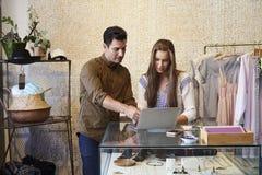 Giovane e donna che lavorano insieme nel negozio di vestiti Immagini Stock Libere da Diritti