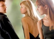 Giovane e donna che osservano faccia a faccia e giovane Fotografia Stock