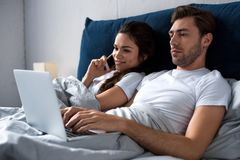 Giovane e donna che per mezzo dei dispositivi digitali mentre trovandosi fotografie stock