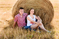 Giovane e donna che posano in un campo vicino ad una balla di fieno Fotografie Stock