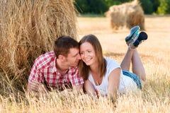 Giovane e donna che posano in un campo vicino ad una balla di fieno Immagine Stock