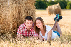 Giovane e donna che posano in un campo vicino ad una balla di fieno Fotografia Stock