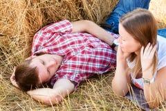Giovane e donna che posano in un campo vicino ad una balla di fieno Fotografia Stock Libera da Diritti