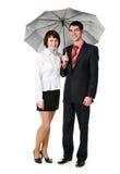 Giovane e donna che si levano in piedi sotto un ombrello. Fotografia Stock Libera da Diritti
