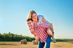 Giovane e donna divertendosi in un campo raccolto vicino ad una balla di fieno Fotografia Stock