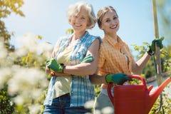 Giovane e donna senior che posa per la foto nel loro giardino immagini stock libere da diritti