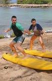 Giovane e giovane donna che imparano praticare il surfing Fotografie Stock Libere da Diritti