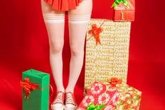 Giovane e ragazza capa rossa graziosa in un mini vestito da Santa Claus su un fondo rosso neutrale fotografie stock