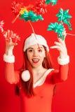 Giovane e ragazza capa rossa graziosa in un mini vestito da Santa Claus su un fondo rosso neutrale immagine stock