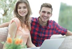 Giovane e ragazza che si siedono davanti ad un computer portatile aperto Immagine Stock