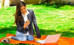 Giovane e ragazza felice con il computer portatile nel parco facendo uso del suo cellulare Fotografia Stock