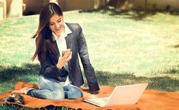 Giovane e ragazza felice con il computer portatile nel parco facendo uso del suo cellulare, effetto d'annata Fotografia Stock Libera da Diritti