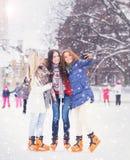 Giovane e ragazza graziosa che pattina sulla pista di pattinaggio sul ghiaccio all'aperto dell'aria aperta ai wi Immagini Stock