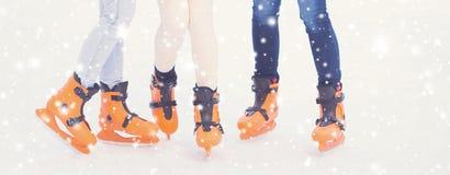 Giovane e ragazza graziosa che pattina sulla pista di pattinaggio sul ghiaccio all'aperto dell'aria aperta ai wi Fotografia Stock