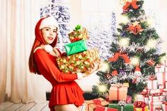 Giovane e ragazza rossa graziosa del letto in un mini mini vestito da Santa Claus su un fondo di natale fotografia stock