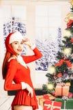 Giovane e ragazza rossa graziosa del letto in un mini mini vestito da Santa Claus su un fondo di natale fotografie stock libere da diritti