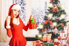 Giovane e ragazza rossa graziosa del letto in un mini mini vestito da Santa Claus su un fondo di natale immagine stock libera da diritti