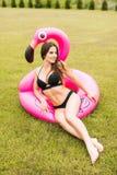 Giovane e ragazza sexy divertendosi e ridendo e divertendosi sull'erba vicino allo stagno su un fenicottero rosa gonfiabile in un fotografia stock libera da diritti