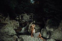Giovane e soggiorno sexy della donna sul costume da bagno d'uso della roccia sulla bella cascata nella giungla accanto alla casca fotografia stock libera da diritti