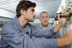 Giovane e tecnico anziano durante il loro lavoro Immagini Stock Libere da Diritti