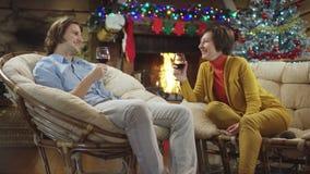 Giovane e vino felice delle bevande della donna adulta ed avere una conversazione sul Natale video d archivio