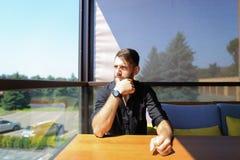 Giovane ecologo maschio che si siede all'ufficio sul sofà con gli alberi nel fondo fotografia stock libera da diritti